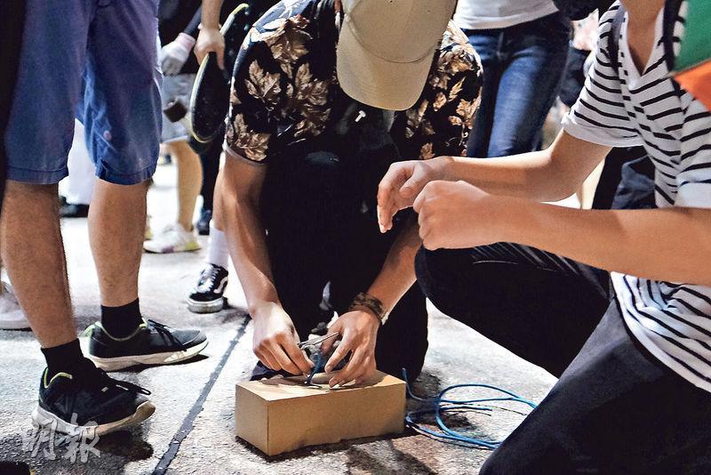 大批市民昨晚響應7.21集會號召,在元朗大馬路聚集,有示威者即時以紙盒及電線製作「詐彈」,並放置在大馬路及大棠路一帶的馬路中心,未見警方派出爆炸品處理課人員到場處理。(馮凱鍵攝)