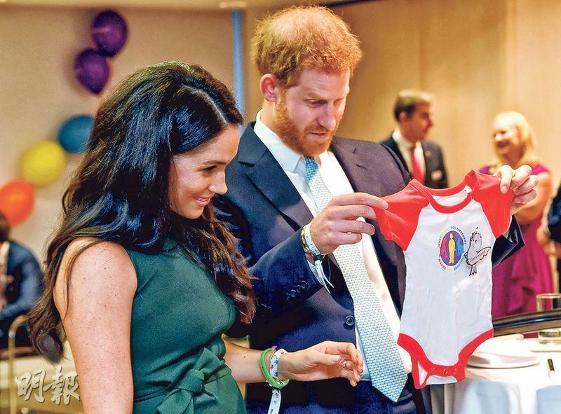 英國哈里王子(右)和夫人梅根上周二出席倫敦的兒童慈善組織WellChild的年度頒獎禮活動,其間兩人注視一件在場者送給他們兒子阿奇的衣物。(法新社)