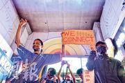 有網民號召昨晚在重慶大慶外「快閃」唱歌,感激少數族裔周日派水支持示威者。「快閃」尾聲,一名少數族裔(左)及黑衣年輕男子(右)一起舉「WE CONNECT」標語牌,在場者見狀一同高呼「Fight for freedom, Stand with Hong Kong」。(鄧宗弘攝)