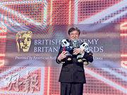 成龍拿着一對熊貓公仔上台領獎。
