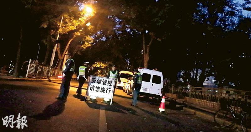 京西賓館昨日保安嚴密。賓館四圍的路口都設有警車和警察駐守,重要路口還有軍警雙崗警戒。圖為警察在賓館周邊路段作交通管制。(明報記者攝)