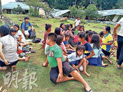 菲律賓哥打巴托省杜路南鎮昨天發生強烈地震,一群師生在倒塌的校舍外空地暫避。(法新社)