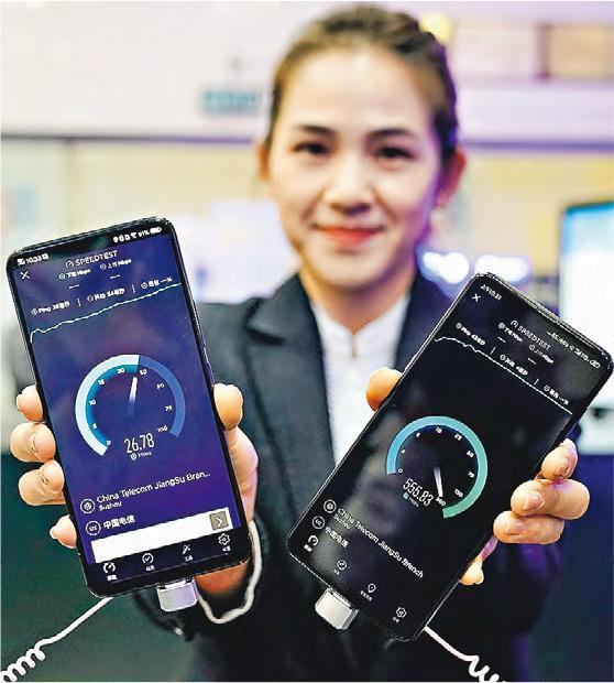 內地三大運營商昨日正式發布各自的5G套餐。在中國電訊北京公司朝陽門營業廳,工作人員昨展示中國電信4G服務與(左,26.78Mbps)5G服務(右,555.83Mbps)的實時下載速度,可見兩者網速差距之大。(新華社)