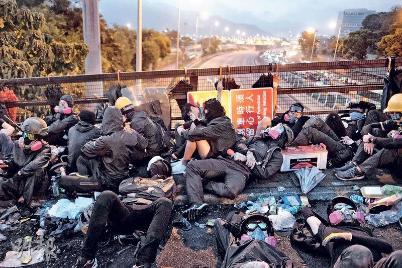 前晚中大爆發警民衝突,警方撤退後,昨晨中大二號橋有數十人聚集,有人席地而睡,當時吐露港仍無法通車。(馮凱鍵攝)
