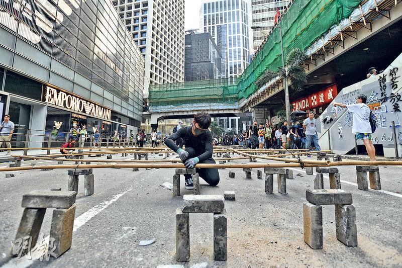 中環昨連續第3日有市民聚集及堵路,有示威者昨午在德輔道中以磚頭及竹枝等雜物設路障,阻止車輛前進。(黃志東攝)