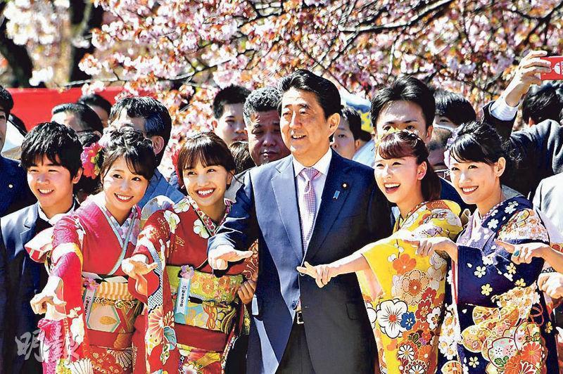 日本首相安倍晉三(中)被指涉濫用公帑舉行賞櫻會,酬謝政治支持者,因此取消明年賞櫻會作檢討。圖為今年4月賞櫻會安倍與參加者合照。(讀賣新聞)