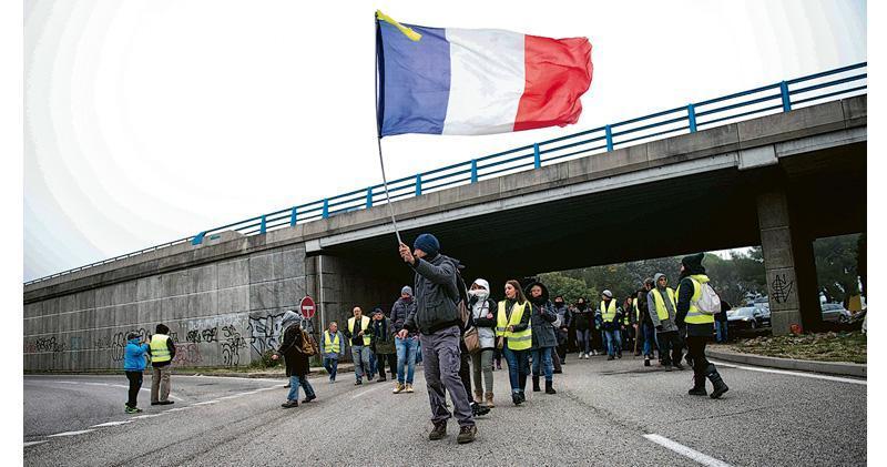 在法國「黃背心」運動一周年前夕,東南部城鎮索爾格昨日有示威者佔領高速公路出口,其間有人揮舞法國國旗。(法新社)