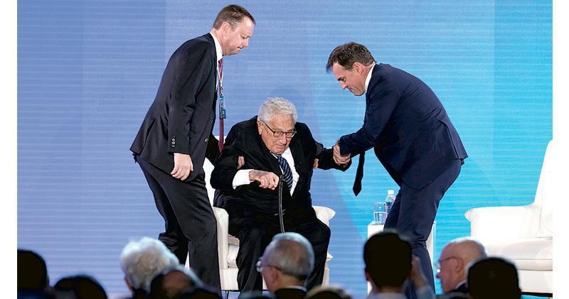 美國前國務卿基辛格昨日出席在北京舉行的2019年新經濟論壇。圖為現年96歲的基辛格在兩名工作人員攙扶下落座。(路透社)