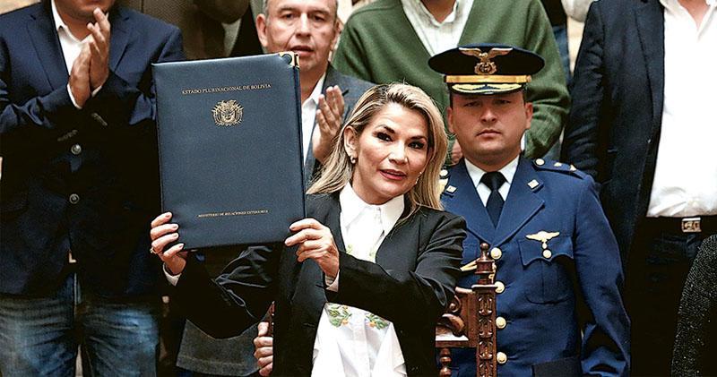 玻利維亞臨時總統阿涅斯(中)周日簽署新法案,宣告上月20日的選舉結果無效,並準備在120天內舉行新大選,但前總統莫拉萊斯將被禁止參選。(路透社)