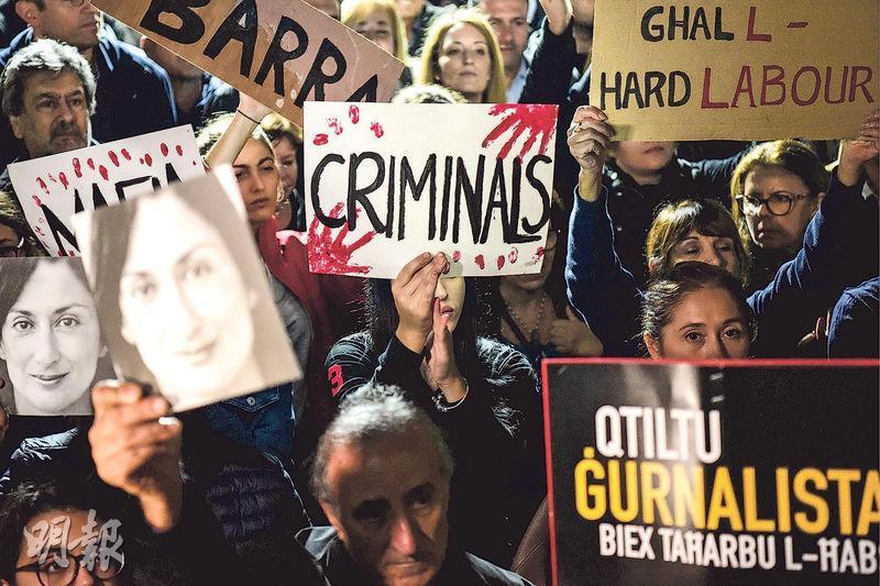 在馬耳他首都瓦萊塔的總理辦公室外,上周五有民眾手持女記者加利齊亞的肖像海報和標語牌,要求嚴懲兇手。(法新社)