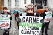聯合國氣候大會周二起揭幕前一天,一些動物保護組織人士在主辦地馬德里示威,主張「肉食是氣候變化首要原因」。(法新社)