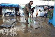 法國南部的市鎮芒代利厄拉納普爾(Mandelieu-la-Napoule)經歷暴雨及水浸後,當地民眾周一合力清理街道上的污泥。(法新社)