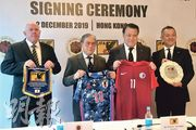 香港足總會長霍震霆(左二)及日本足協會長田嶋幸三(右二)昨在簽署儀式上交換紀念品,包括印有二人名字的代表隊球衣。(余瑋攝)