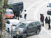 警方在何文田常樂街以一輛七人車及一輛客貨車前後包抄,將疑犯駕駛的白色私家車及的士截停,拘捕7人,警方其後押解兩名疑犯返回現場蒐證。(黃煒堯攝)