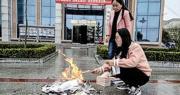 甘肅慶陽市鎮原縣圖書館在門口高調「焚書」,事件在內地網絡引發強烈反響。圖為兩名工作人員在圖書館門口將所謂的禁書燒毁。(網上圖片)