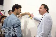 香蕉被吃掉後,畫廊東主貝浩登(右)將一根香蕉重新黏在牆上。(路透社)