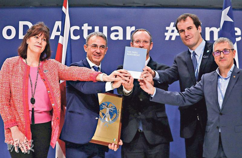 獲委任為下屆聯合國氣候大會主席的英國前任能源及潔淨增長策略國務大臣彭麗雅(左),與意大利環境部長科斯塔、本屆氣候大會高級氣候倡導者穆尼奧斯和西班牙環境大臣莫蘭等,昨在馬德里氣候大會上一起捧着一冊《巴黎氣候協定》,以示守護協議精神的決心。(路透社)