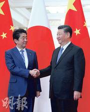日本首相安倍晉三(左)昨天與國家主席習近平在北京會談時表示,「極其重視」預定於明年春天的習近平作為國賓訪日之行。(法新社)
