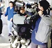 昨日大埔超級城外,有防暴警(左)欲拘捕示威者時,捉着一名蒙面的懷疑便衣警(右),數秒後有另一懷疑便衣警輕拍防暴警,防暴警始放開藍衣便衣警。(蘋果日報直播截圖)