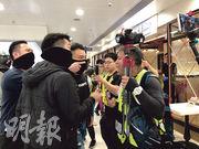 立場新聞記者陳朗昇(前右一)昨於大埔超級城直播,其間追問前方持警棍者是否便衣警察,與數名便衣警察口角,並遭檢查身分證。(何郁慧攝)
