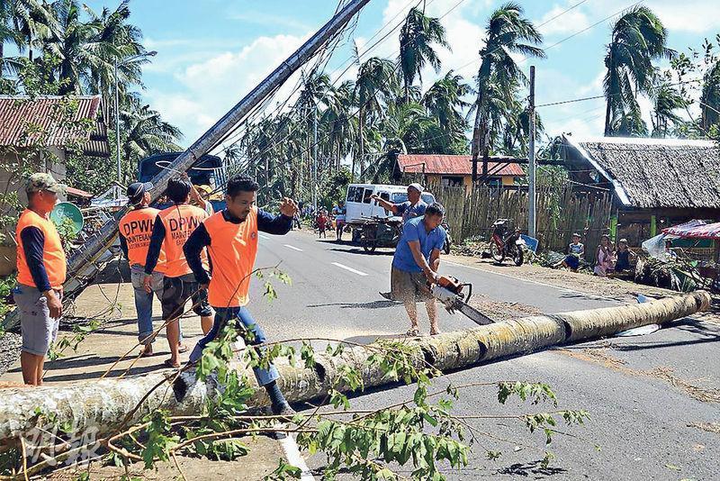 菲律賓中部受颱風巴蓬吹襲,多處電線杆和大樹倒下,工人昨日忙於搶修。(法新社)