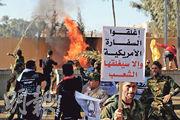 什葉派民兵舉牌要求伊拉克政府關閉美國大使館,否則人民將自己動手關掉它。(路透社)