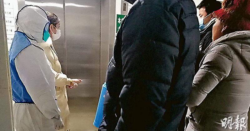 21歲女患者明明(左二)在全副防護裝備的醫護人員和父母(近處兩名背對者)陪同下,轉至金銀潭醫院隔離治療。