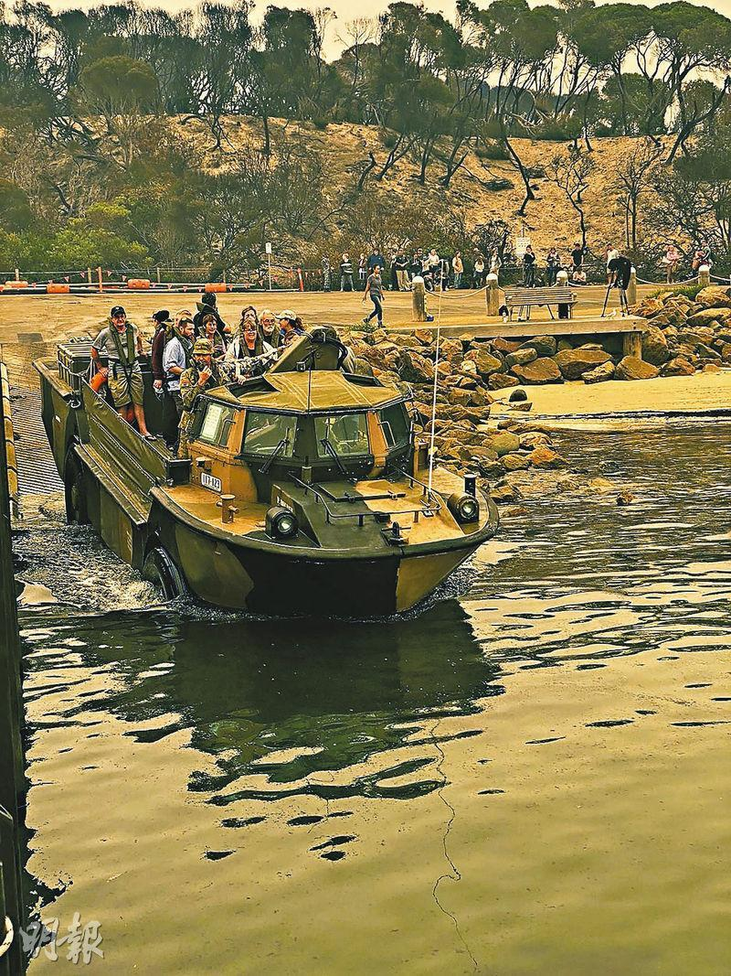 澳洲海軍昨日抵達馬拉庫塔(Mallacoota),協助在海邊被火災圍困的民眾疏散。(法新社)