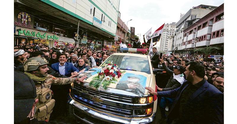 伊拉克數以萬計民眾昨天在巴格達街頭,簇擁追隨着蘇萊曼尼的靈車,部分人高叫「美國去死」的口號。(法新社)