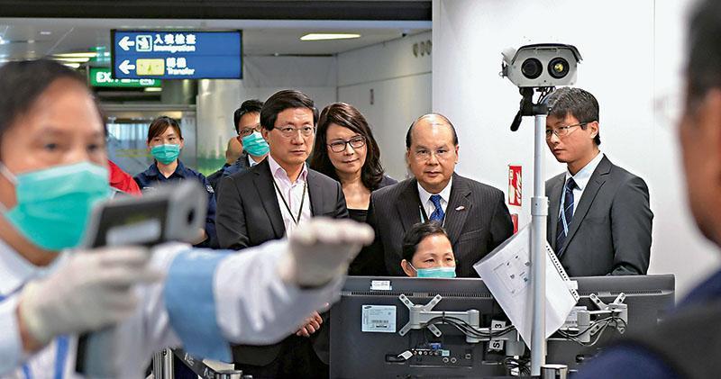 政務司長張建宗(右二)昨到機場閘口視察武漢抵港航班檢疫措施,圖為工作人員用紅外線熱像儀監測旅客體溫。