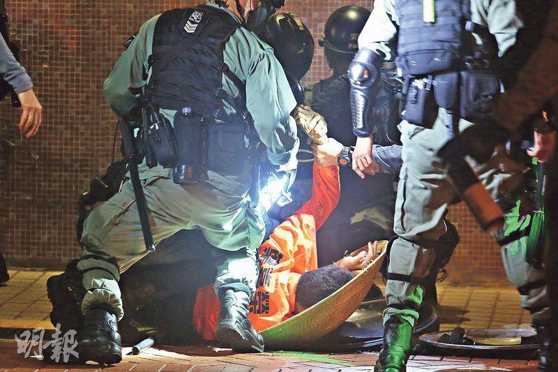 西貢區議員李嘉睿的助理葉嘉榮被防暴警按壓在地上,當時他正持一藤製盾牌,他臉部被噴上藍色水劑。(伍浦鋒攝)