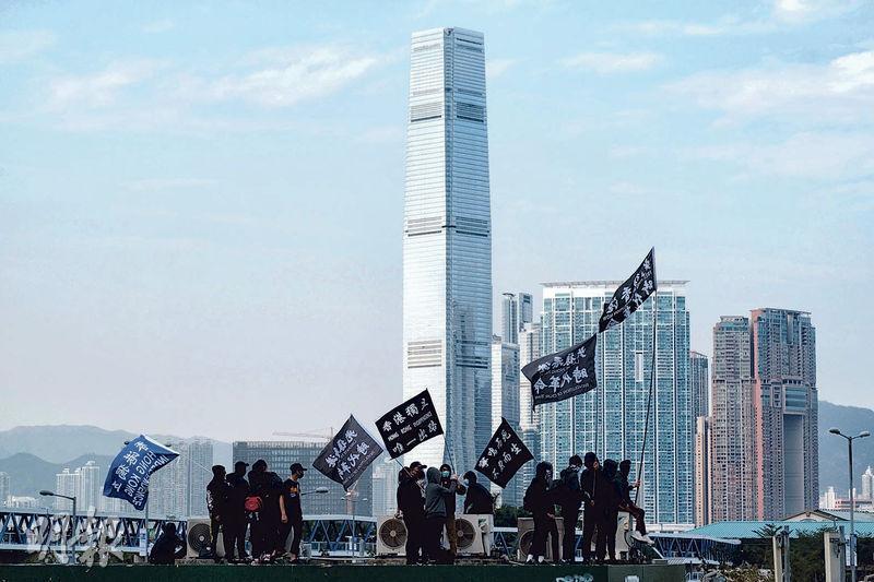 昨於中環的集會舉行期間,多名黑衣示威者在愛丁堡廣場附近的天星碼頭多層停車場頂層,高舉「光復香港 時代革命」旗幟。(馮凱鍵攝)