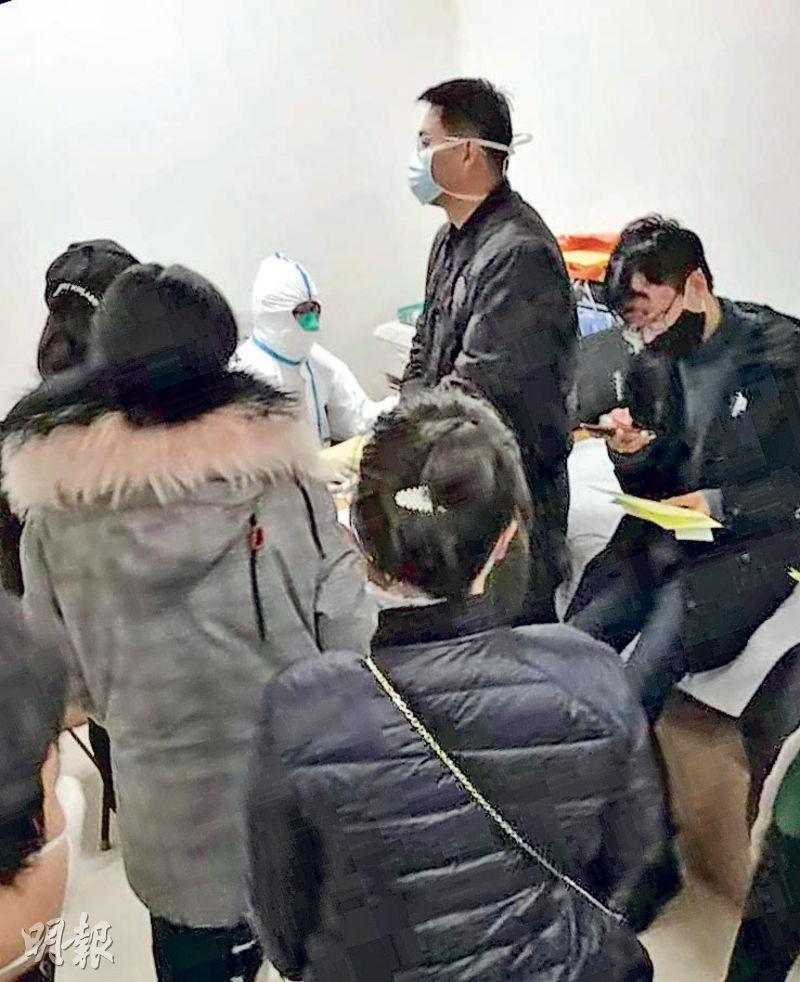 北京昌平區清華長庚醫院發燒門診,大量患者等待分診排查,全副防護的醫生向求醫者詢問病情徵狀,及最近有否到過武漢或接觸從武漢歸來者。(明報記者攝)