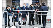 武漢封城抗疫,暫時關閉機場、火車站、地鐵和水路交通。圖為昨日上午10時,戴着口罩的工作人員關閉武漢漢口火車站離漢通道。(中新社)