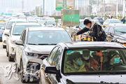 武漢昨晨10時起採取封城措施,當地衛生和防疫工作小組工作人員在路中檢查汽車乘客的體溫。(路透社)