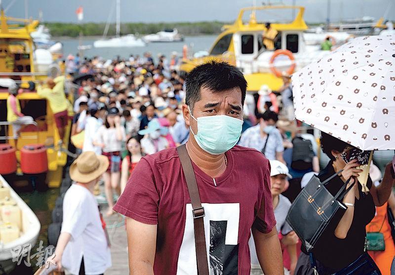 昨在印尼峇里島遊覽的中國旅客,部分人戴上口罩作為防範武漢肺炎措施。(法新社)