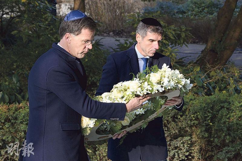荷蘭首相呂特(左)昨趁波蘭奧斯威辛集中營解放75周年,在阿姆斯特丹儀式上獻花圈。(法新社)
