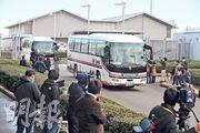 從武漢乘搭專機返國的日本國民昨日抵達東京羽田機場後,隨即轉乘政府安排的專車,到醫院接受檢查。(法新社)