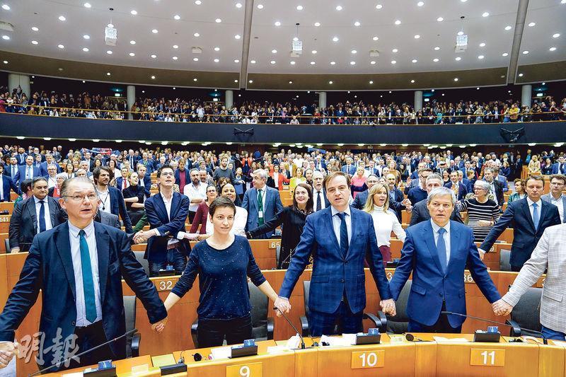 歐洲議會周三通過英國脫歐協議後,議員隨即手牽手,高唱《友誼萬歲》。(中新社)