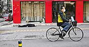 在距離收治武漢肺炎患者的主要醫療中心之一、武漢市第六醫院一個街區之遙,法新社記者前日目睹一名戴口罩、看似年約60多歲的白髮男子,倒卧武漢街頭,手裏仍握着一個膠袋。醫護人員其後到場用藍色氈子遮蓋其身體並載走。(法新社)