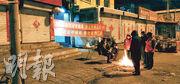 河北承德市一城中村村委會在村口懸掛抗疫橫幅,禁止村外人員入村,並派出多人把守道路。入夜天寒,守路者要烤火禦寒。