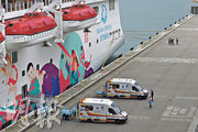 「世界夢號」郵輪因曾接載確診新型冠狀病毒內地旅客,台灣以安全為由拒絕旅客及船員於高雄下船,郵輪昨晨抵達啟德郵輪碼頭,船上所有人需接受衛生檢疫。昨午有曾有發燒症狀的工作人員由救護車送院檢查,其間數名防暴警員(右上方者)遠距離戒備。(鍾林枝攝)