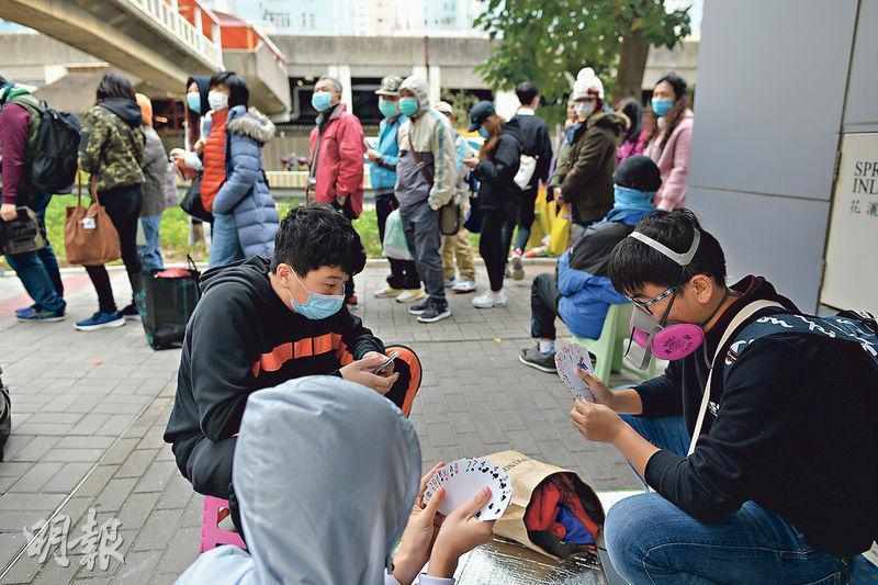 九龍灣有批發公司發售逾萬盒口罩,數千人通宵排隊,眾人各出其謀打發時間,有人拿出摺櫈地席,在街頭玩啤牌消遣。(鍾林枝攝)