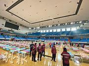 武漢3間專門收治新型冠狀病毒肺炎輕症患者的「方艙醫院」昨日建成。圖為工作人員前日在武漢洪山體育館佈置病牀。(新華社)