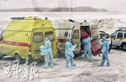 在俄羅斯西伯利亞城市秋明(Tyumen)的機場,醫護人員昨日準備接走由武漢搭包機撤回的國民。(路透社)