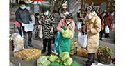 疫情形勢嚴峻,稍不留意,就可能被感染。四川成都推出「流動便民菜市」進入社區,方便市民買餸,市民在選購蔬菜時都做好個人防備,戴上口罩。(中新社)
