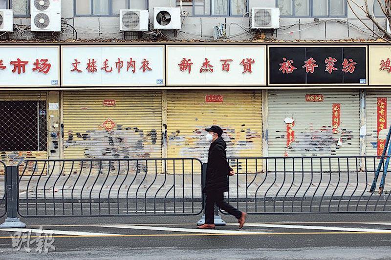 武漢封城禁車,街上商舖關門,人迹稀少,偶爾見到的行人都戴着口罩。(路透社)