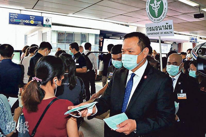 泰國衛生部長阿努廷(前右)周五到BTS車站派口罩予民眾期間,指拒絕戴口罩的西方旅客應被逐出境,他其後就言論道歉。(法新社)