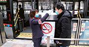 上海昨嚴格執行公共場所體溫檢測和自覺佩戴口罩措施,拒不配合者,工作人員可拒絕其進入。圖為工作人員在公交車站為乘客測量體溫。(中新社)