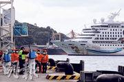 新型冠狀病毒續波及郵輪,上周二從基隆出發、原計劃停靠沖繩那霸遭拒的「寶瓶星號」,昨折返回台接受檢疫後,遊客終可登岸。圖為檢疫人員準備登船。(中央社)